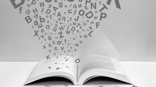 Alphabet flying from open book.