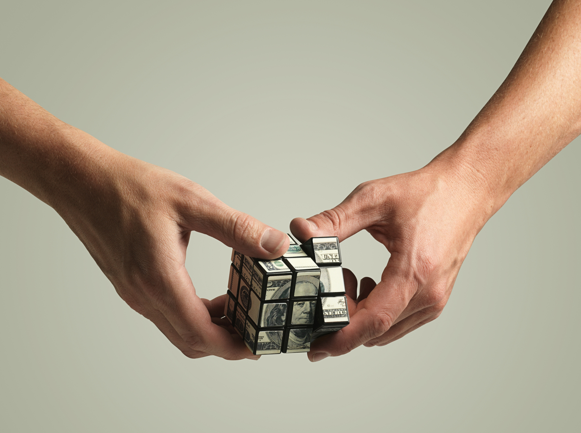 Hands holding rubik's cube made of 100 dollar bill