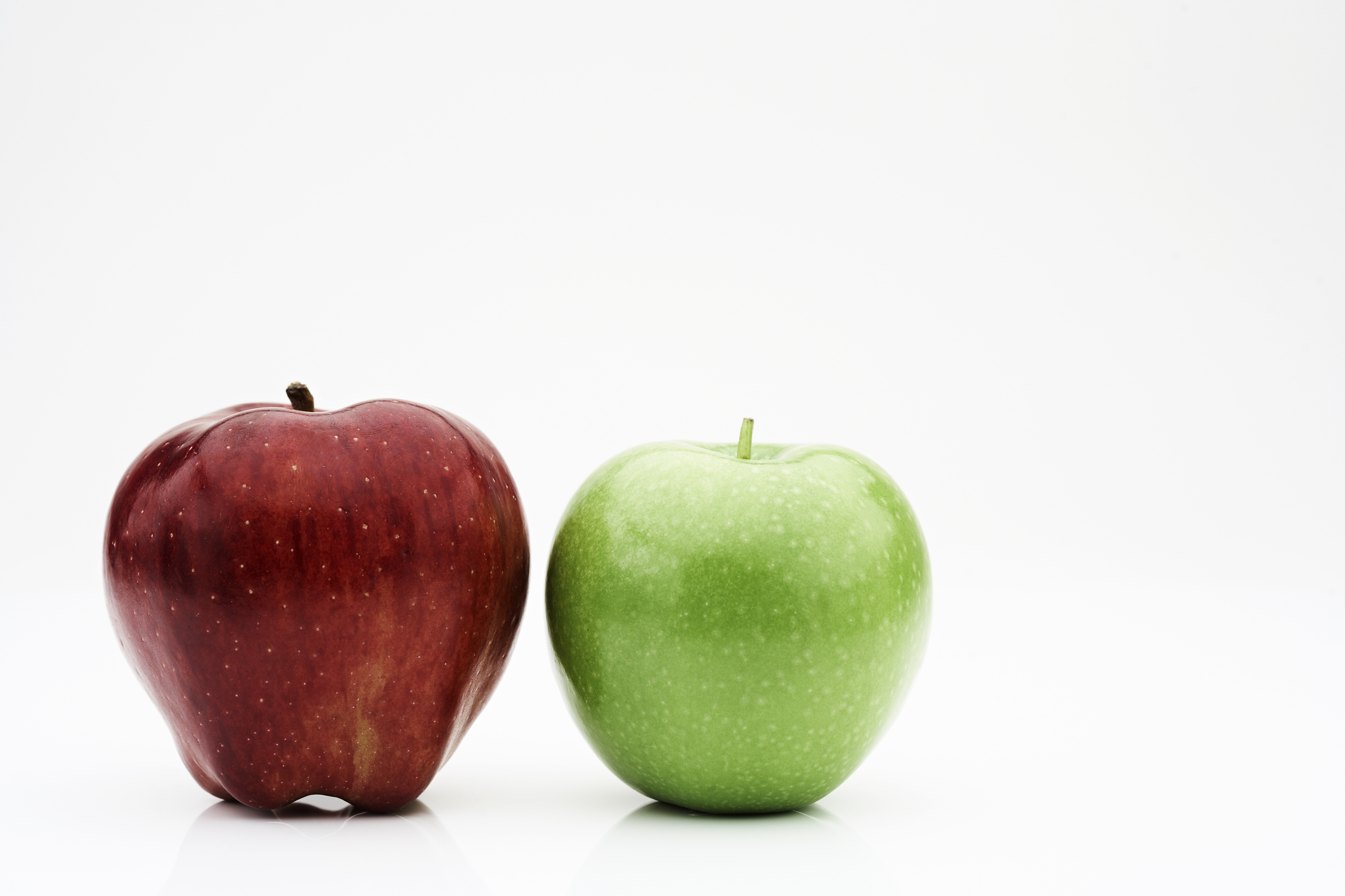 Red and green apple, side by side