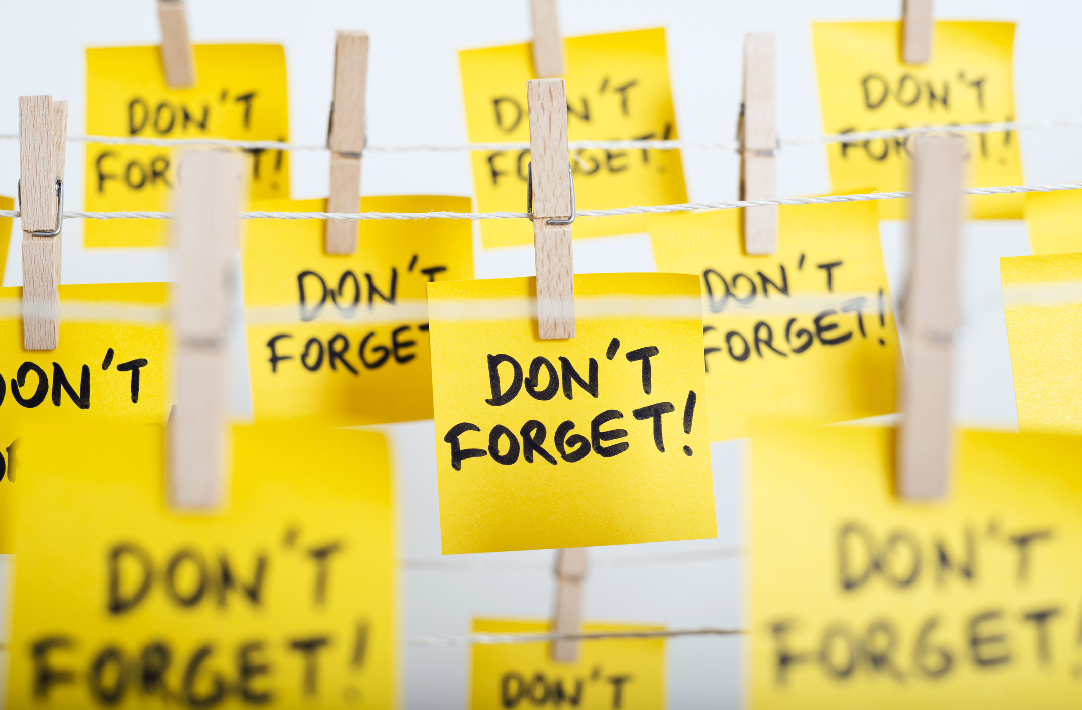 "adhesive note papers with ""don't forget!"" message hanging on the rope"
